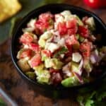 avocado salsa in black bowl with chips.