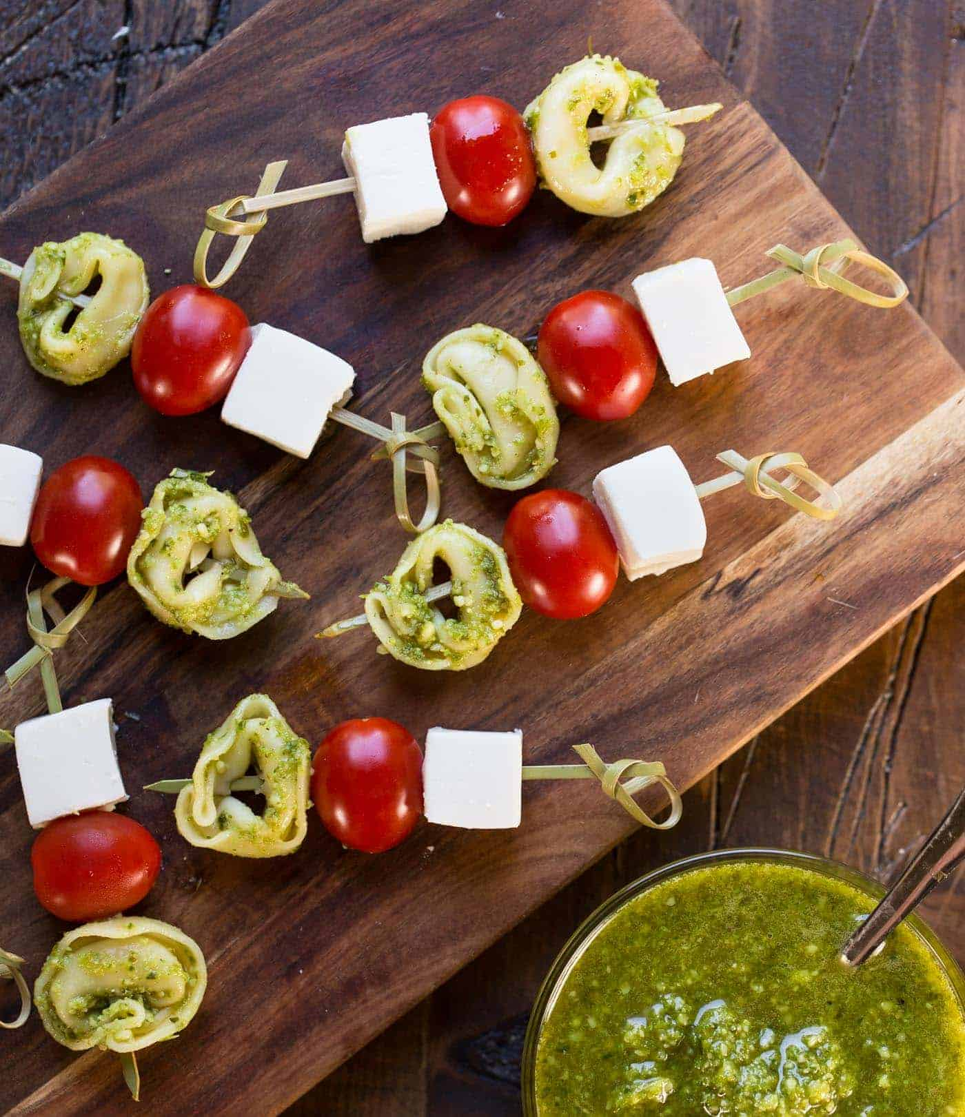 Caprese skewers on wooden cutting board with pesto.