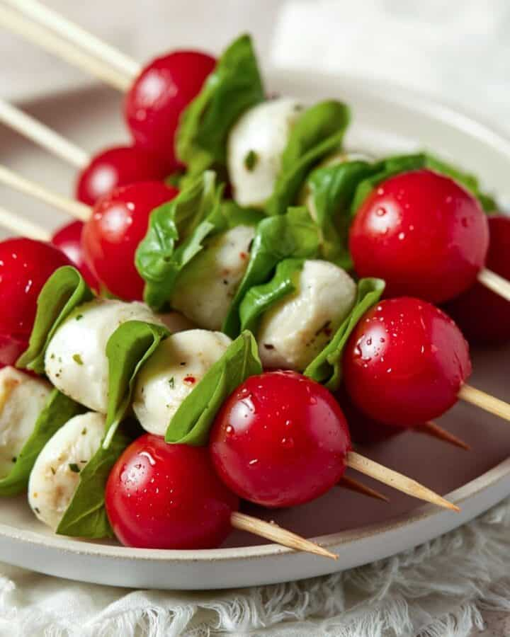 Caprese skewers stacked on top of each other on a gray plate.