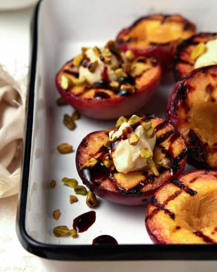 White enamel tray filled with grilled peach halves.