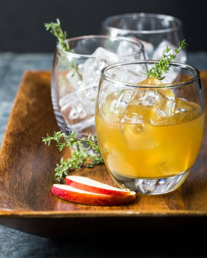 Three low ball glasses on wooden serving tray. First glass is filled with apple cider drink. Garnished with fresh thyme sprigs.