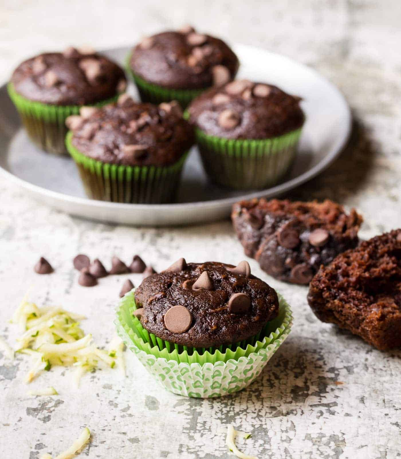 Chocolate Zucchini muffins of table with grated zucchini and chocolate chips.