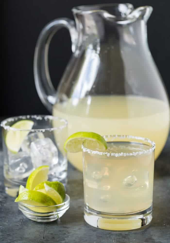 Low ball glass with salted rim and lime wedge garnish filled with golden margarita. Pitcher of golden margaritas in background along with small bowl of limes.
