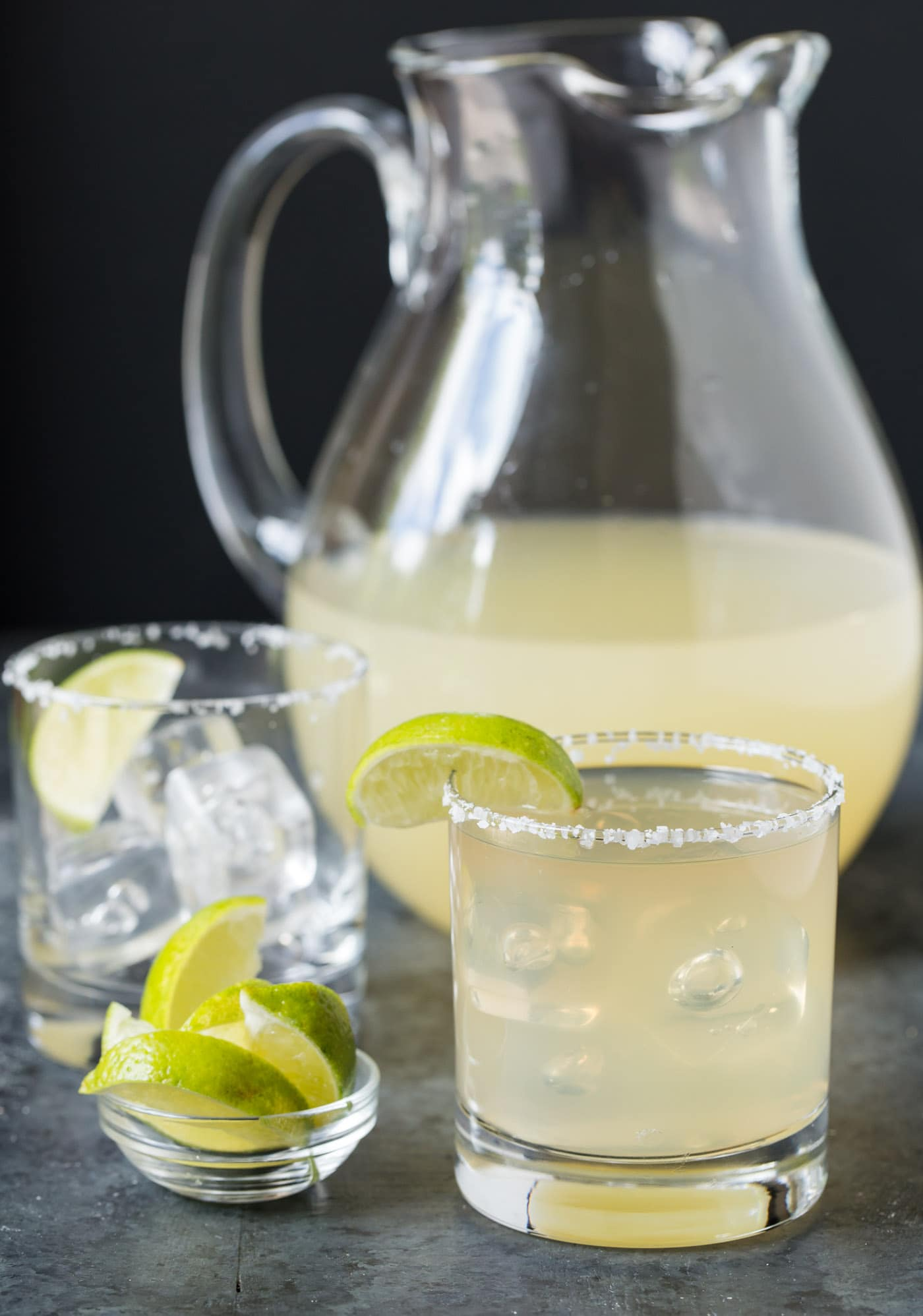 Pitcher of margaritas with filled glass and limes.