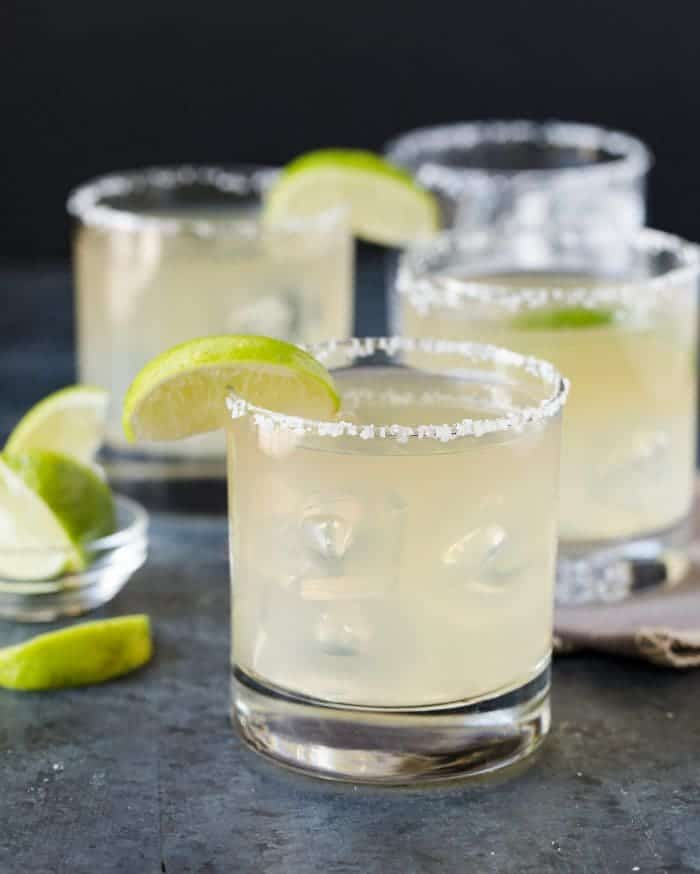 Low ball glasses with salted rims and lime wedge garnishes filled with golden margaritas.