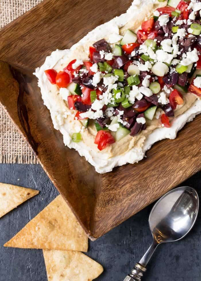 Layered Greek Dip is a healthier spin on a favorite 7-layer appetizer. Loaded with fresh veggies, hummus and a little bit of cream cheese for richness.