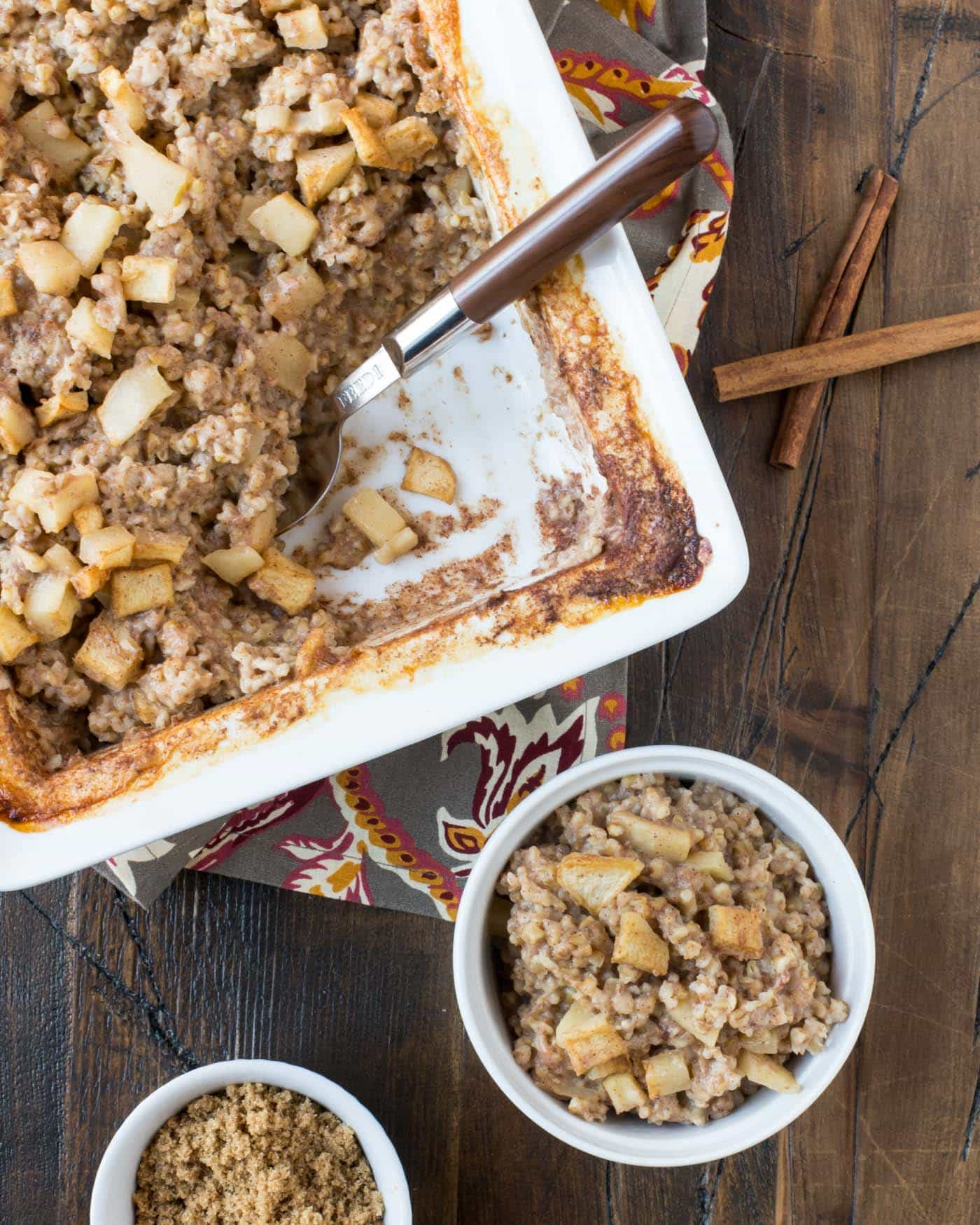 Top down image of white pan filled with baked oatmeal and a brown spoon for serving with a cinnamon stick for garnish.