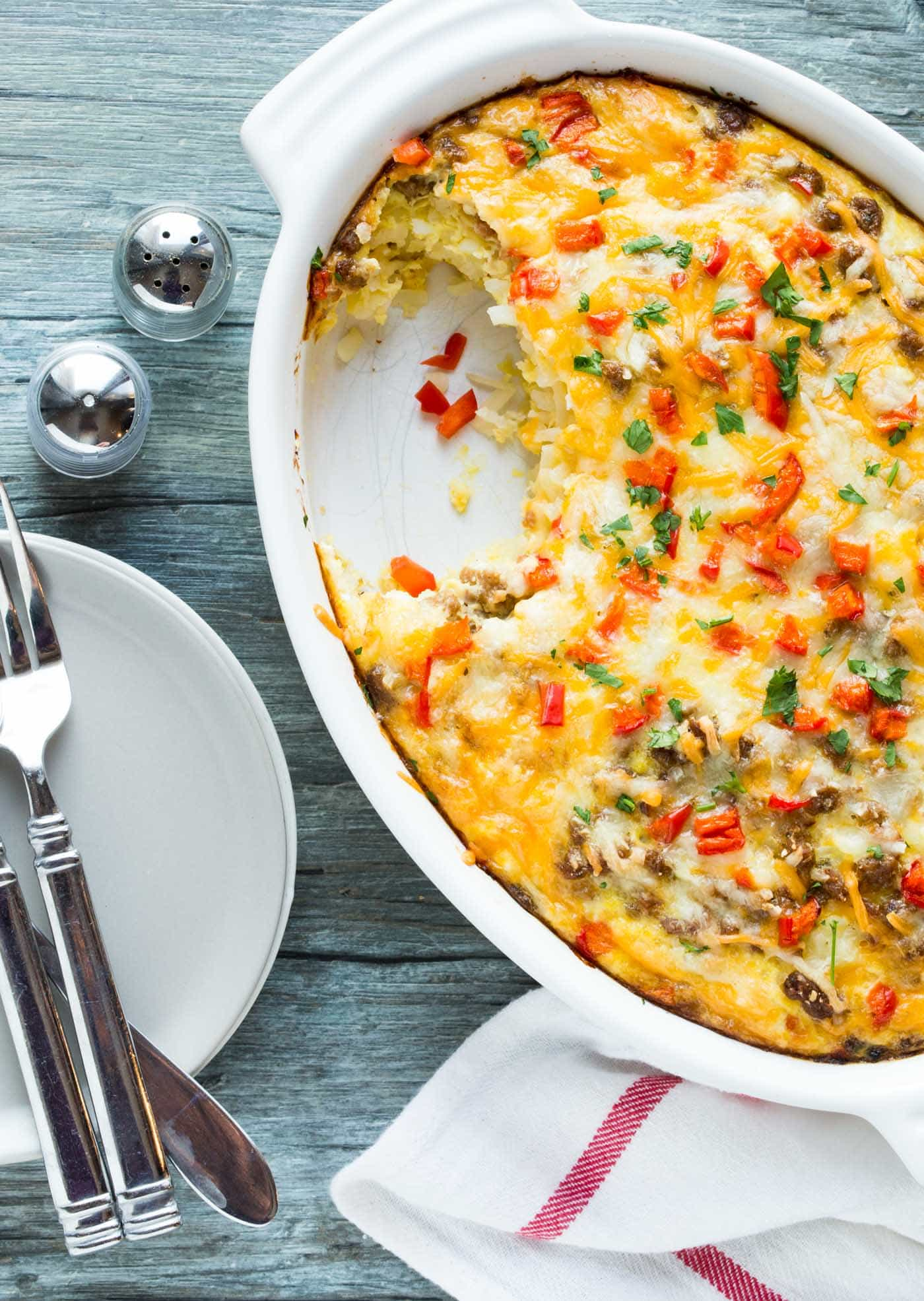 Hash brown egg casserole in a white serving dish with a portion scooped out.