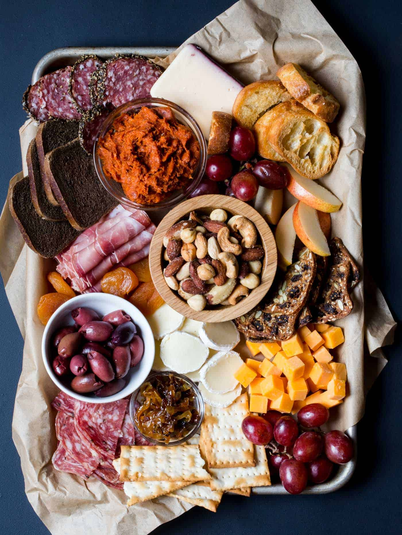 meat and cheese tray with olives, grapes, crostini and apples.