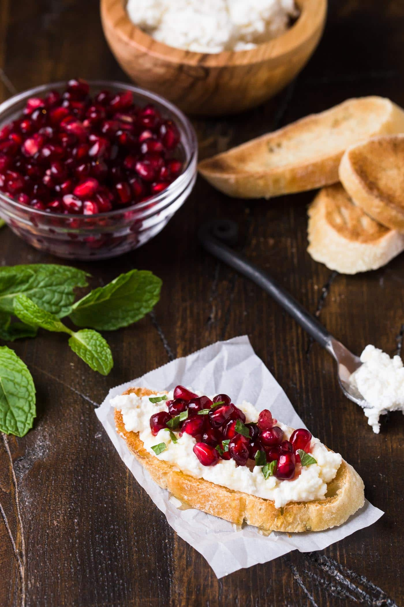 Need a quick and easy appetizer for a holiday party? Look no further than these festive Pomegranate Crostini with Ricotta and Mint!