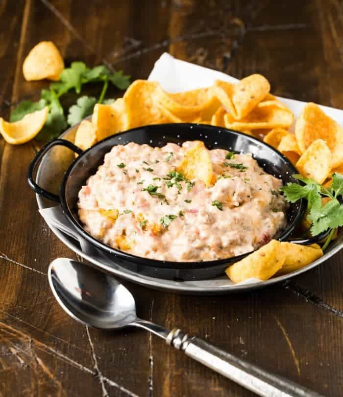 Black serving dish filled with cheesy sausage dip and garnished with chopped cilantro. Corn chips on side for dipping and spoon in front for serving.
