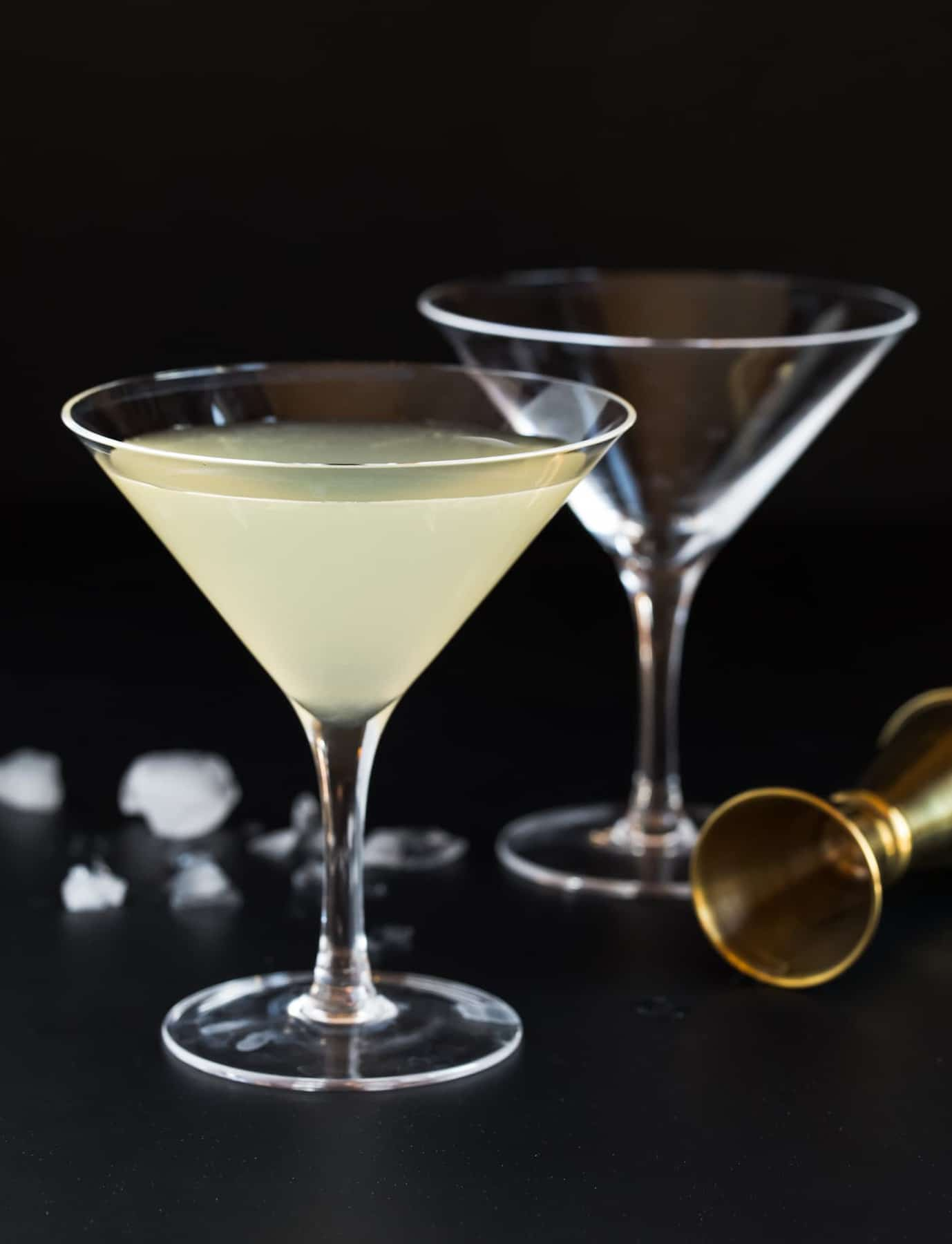 Two martini glasses and a gold jigger on black background. One martini glass is filled with an Elderflower Martini.