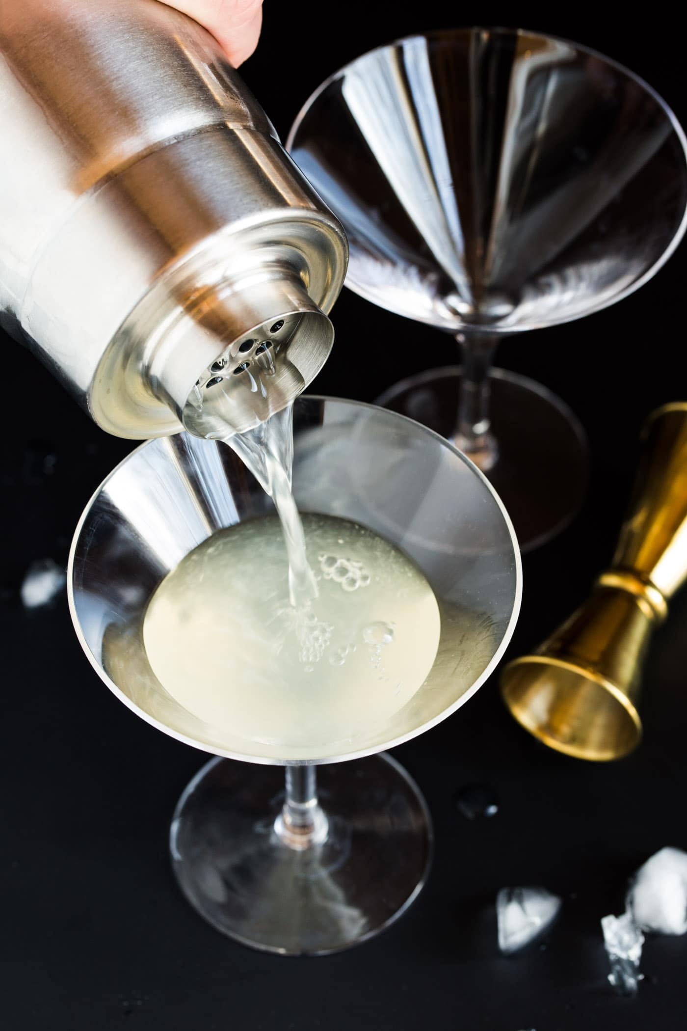 Elderflower Martinis being poured into short martini glasses from silver shaker.