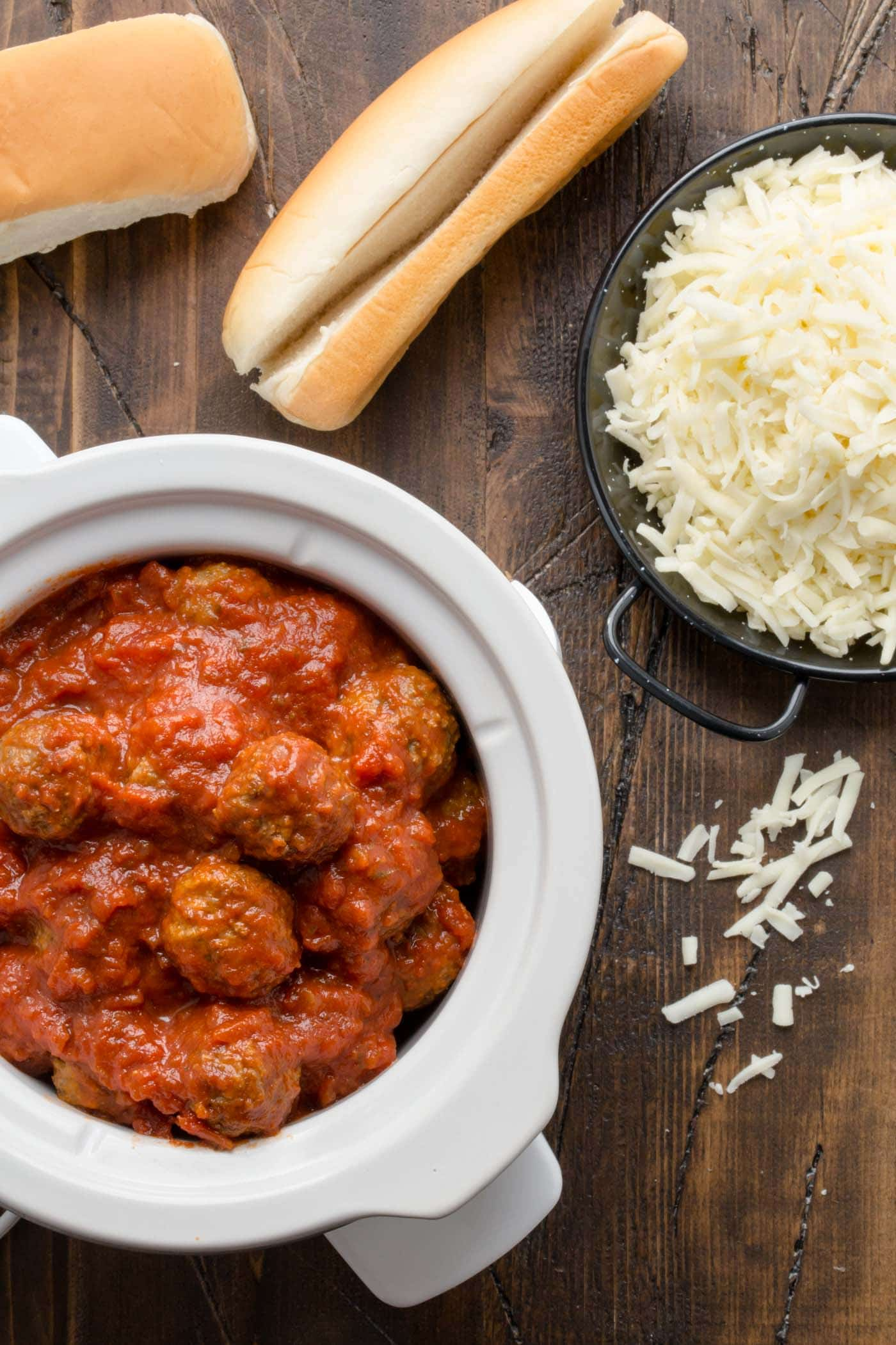Slow Cooker with meatballs and fresh shredded mozzarella with buns.