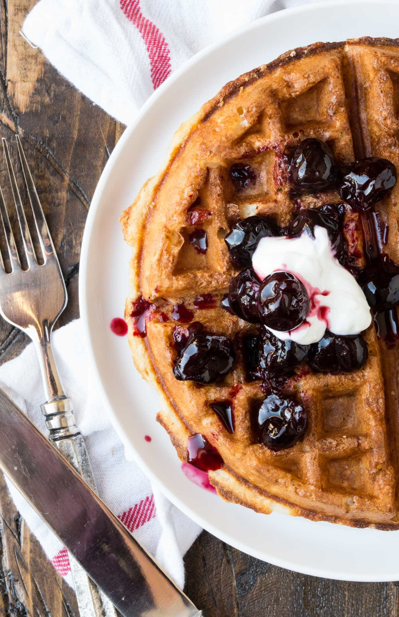 Close up of buttermilk waffle with cherries on white plate.