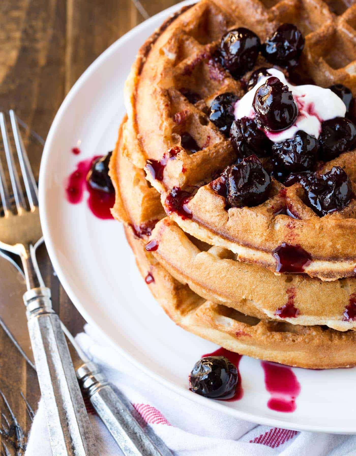 Stack of buttermilk waffles with cherry sauce.