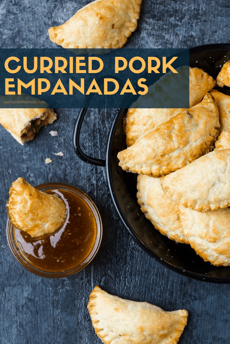 Image of mini curried pork empanadas in a speckled black and white pan. One empanada is dunked in a dipping sauce.