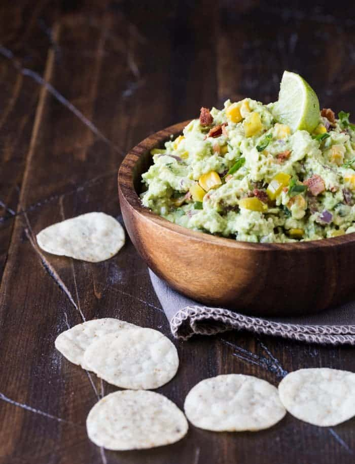 Small wooden bowl filled with corn and bacon guacamole. Garnished with a lime wedge and chips scattered on foreground.