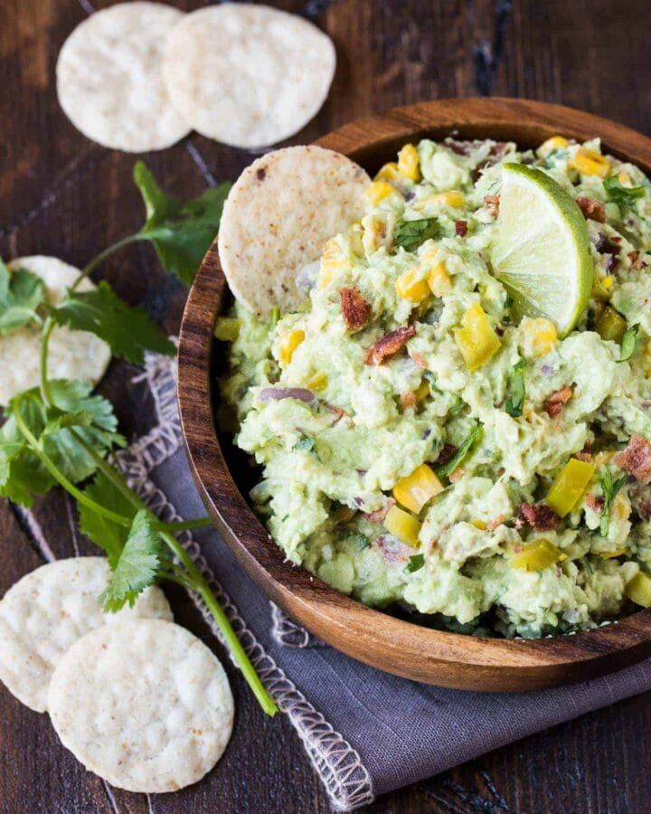 Small wooden bowl filled with Corn and Bacon Guacamole garnished with a lime wedge. Tortilla Chips Scattered on foreground for dipping.