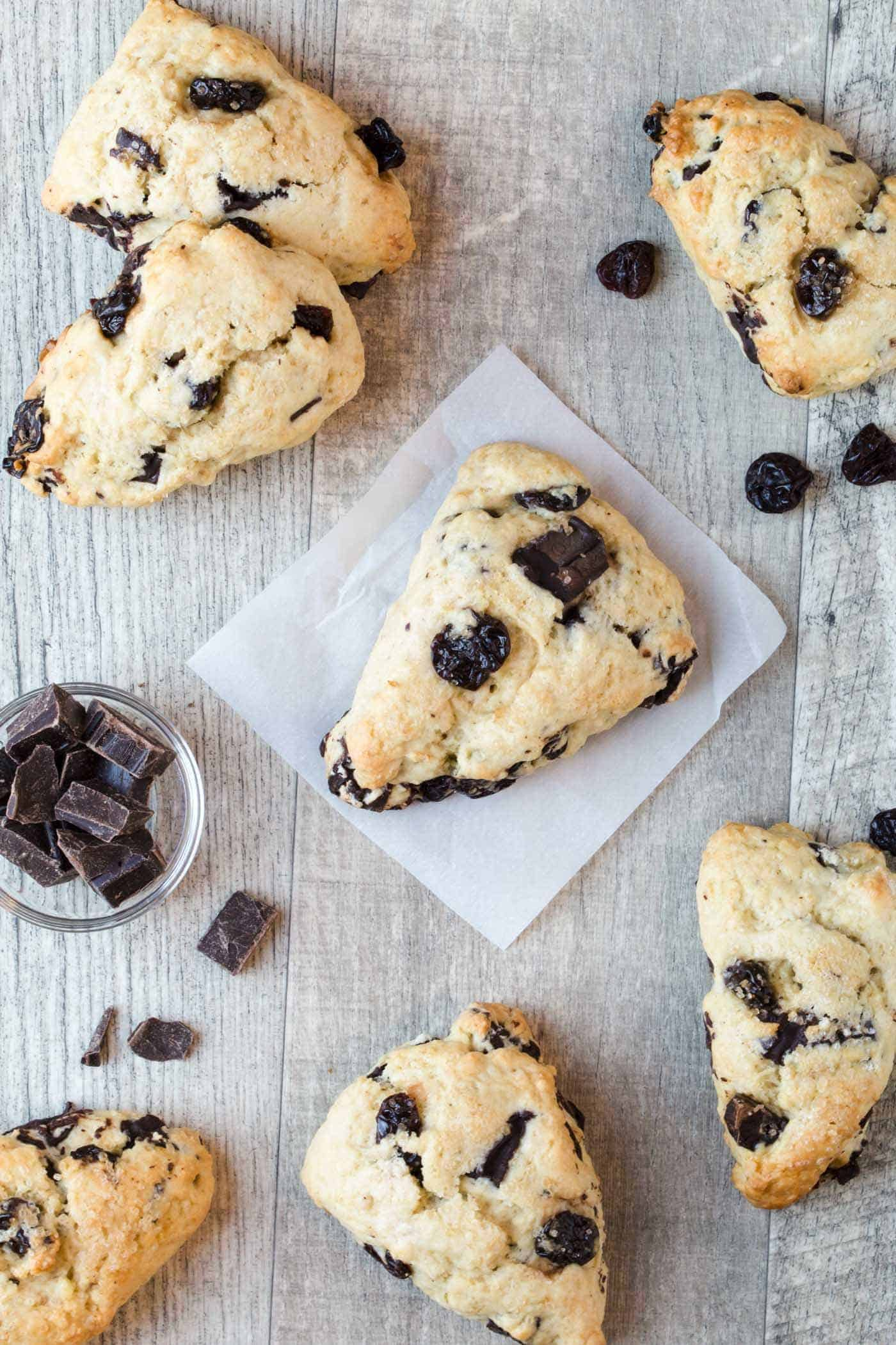 Seven Dark Chocolate Cherry Scones on a wooden board surrounded by dark chocolate chunks and dried cherries.