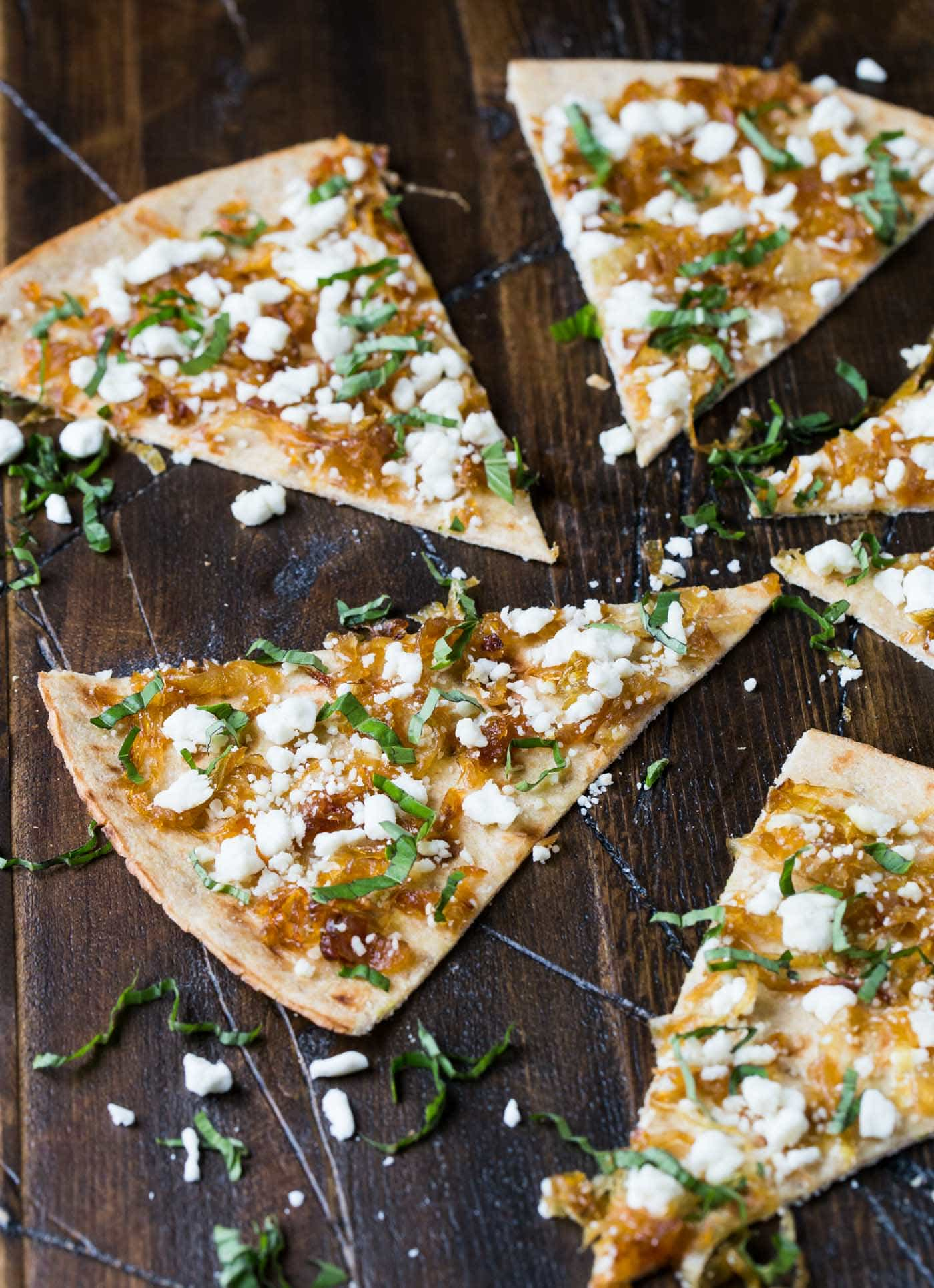 Slices of Flatbread with Goat Cheese and Caramelized Onions on a wooden board.