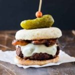 Burger with Irish Cheddar and Bacon on a toasted English muffin and topped with a mini gherkin pickle.