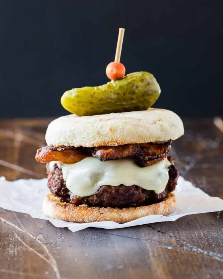 image of a Guinness Burger with Irish Cheddar and Bacon on a toasted English muffin and topped with a mini gherkin pickle. Part of a collection of 4 unique burger recipes for your backyard BBQ.