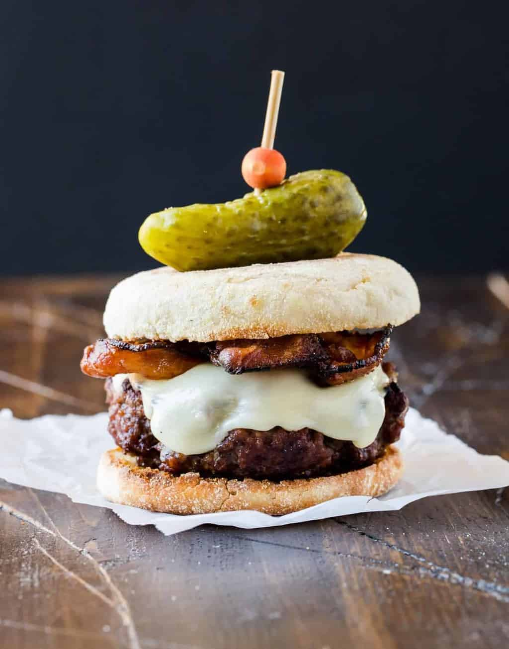 One Guinness Burger with Irish Cheddar and Bacon topped with a mini gherkin pickle and a toothpick skewering the burger.