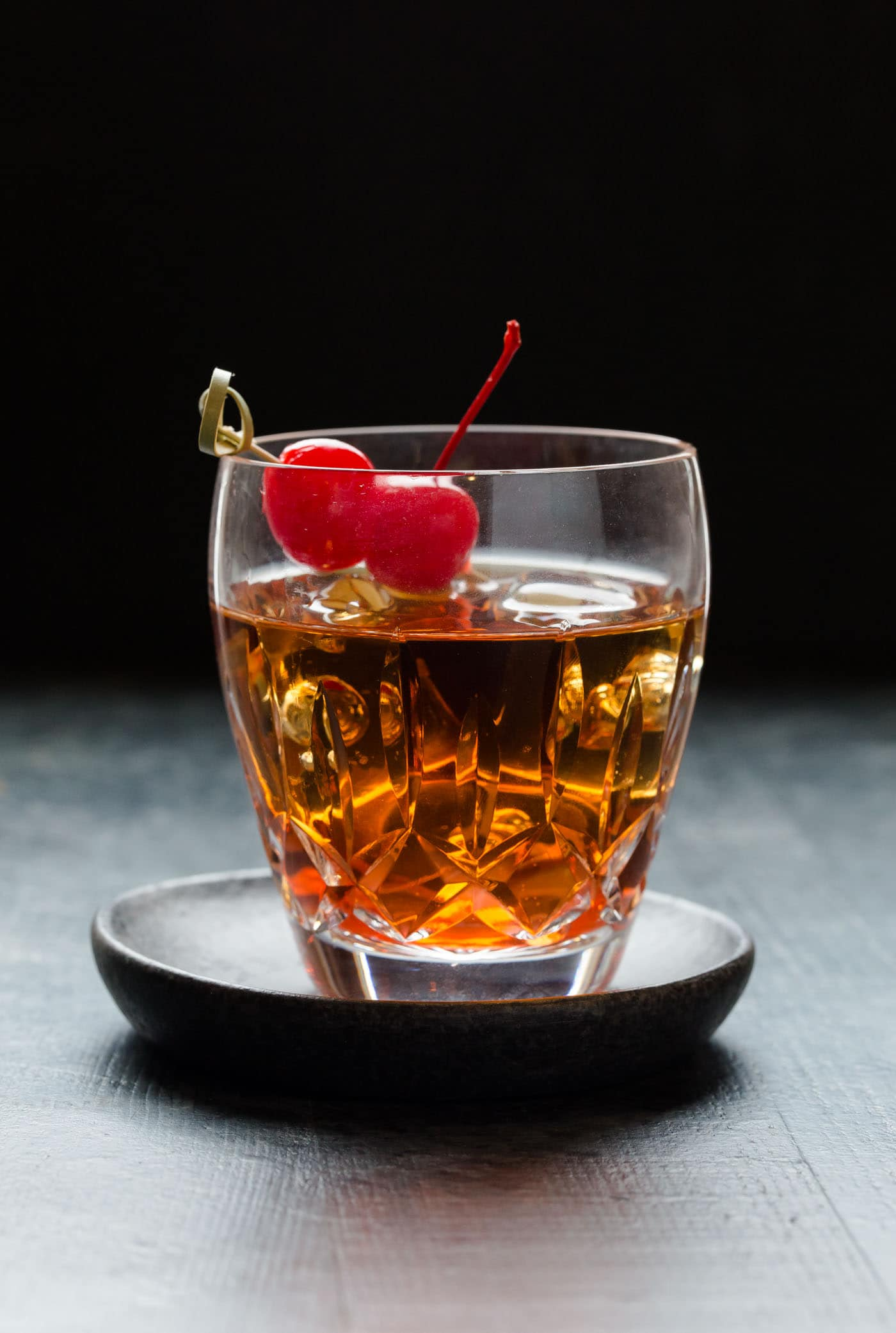 Close up image of Perfect Manhattan Cocktail in a low ball glass filled with ice and fresh cherries for garnish.