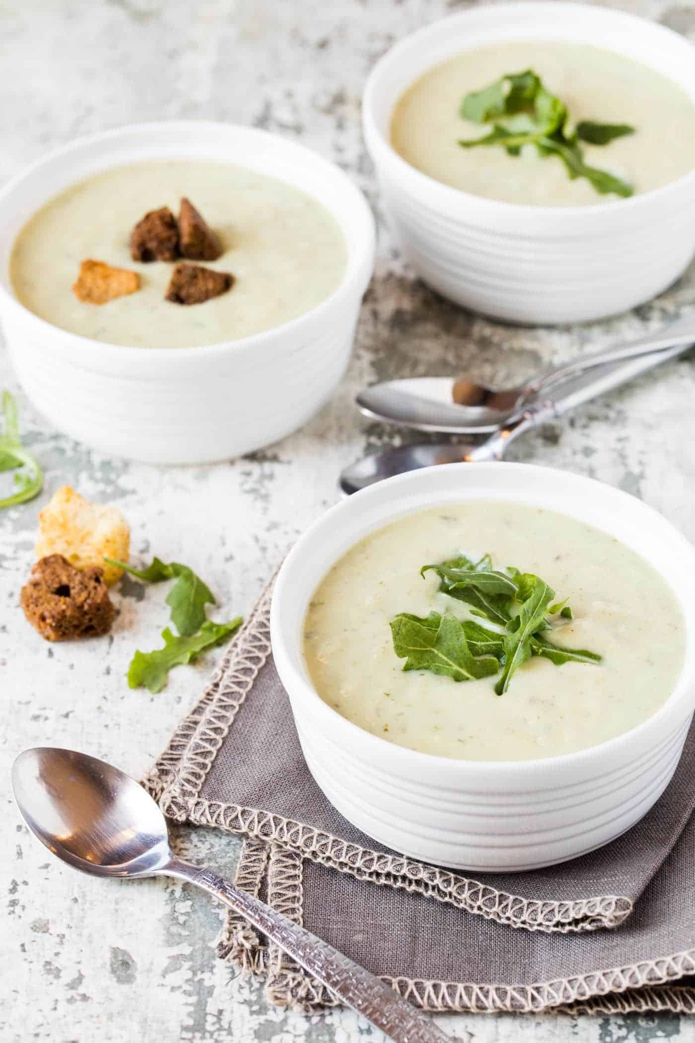 Three white ramekin bowls filled with Roasted Potato Leek Soup with Arugula. One bowl is on a dark gray napkin with a spoon and the other bowls are garnished with croutons and fresh arugula.