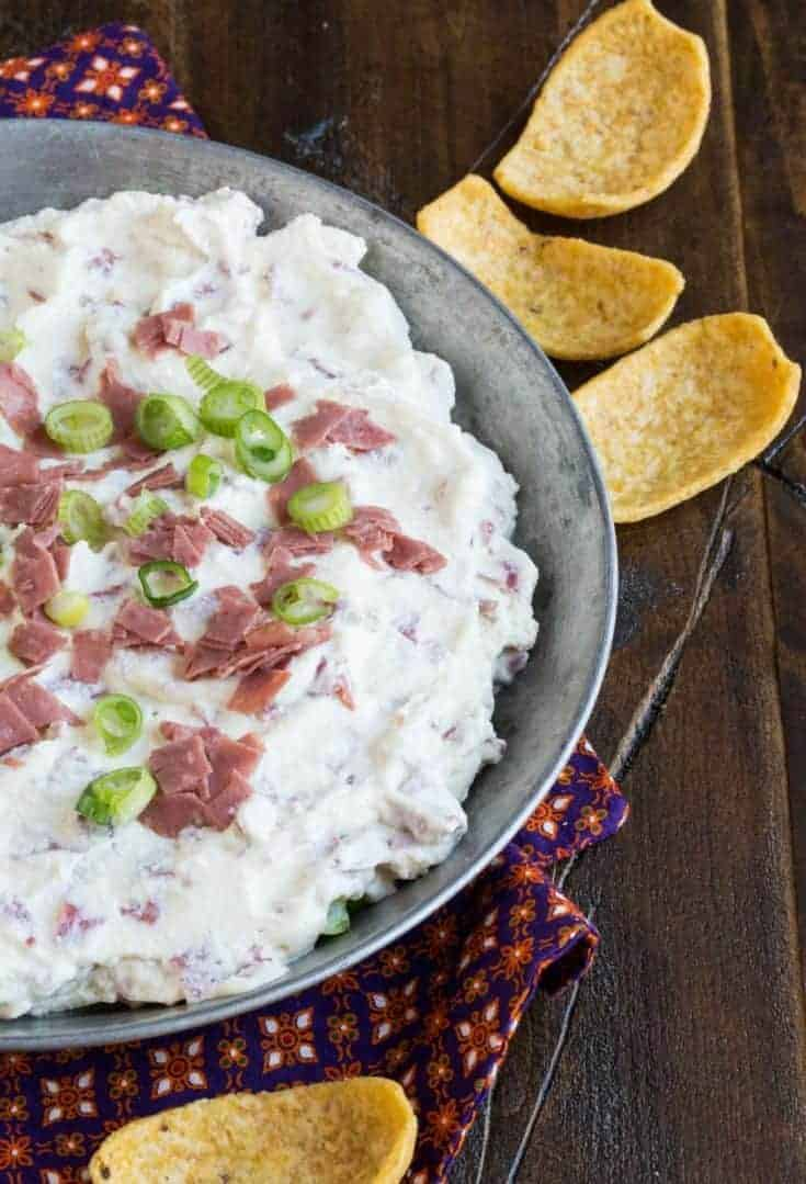 chipped beef dip in a metal baking dish on a dark background with corn chips for eating.
