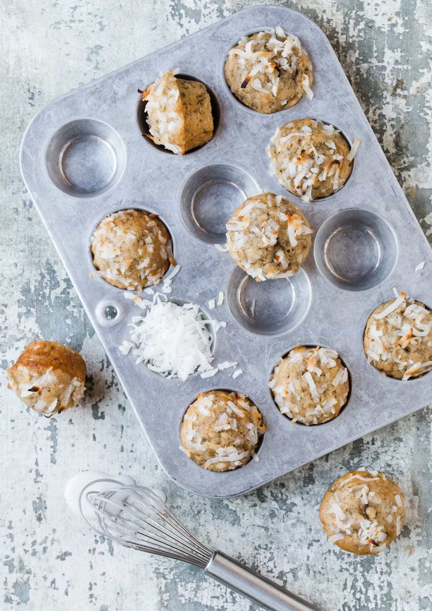 Mini muffin pan filled with Coconut Banana Bread Mini Muffins with Lime Glaze. Garnished with fresh shredded coconut