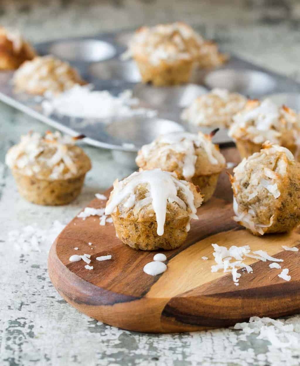 Coconut Banana Bread Mini Muffins with a tangy fresh lime glaze on a wooden serving platter.