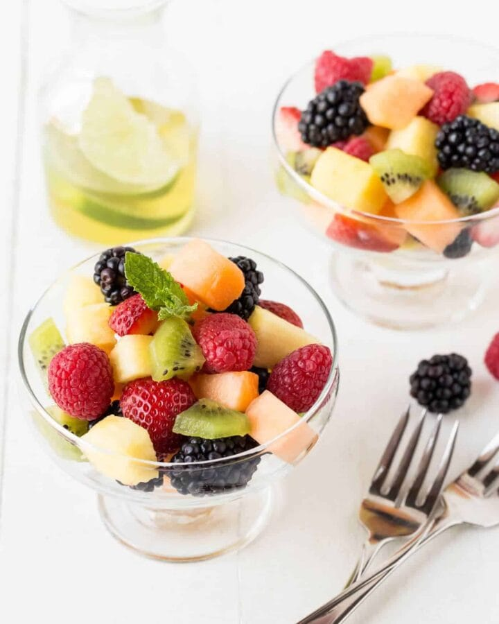 Glass bowls filled with fruit salad, with mint syrup.