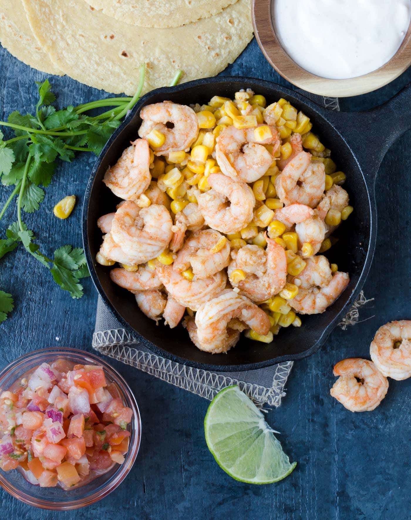 AA pan filled with shrimp and corn with fresh limes and tomatoes.