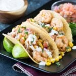 Shrimp tacos on black platter with fresh limes and crema.