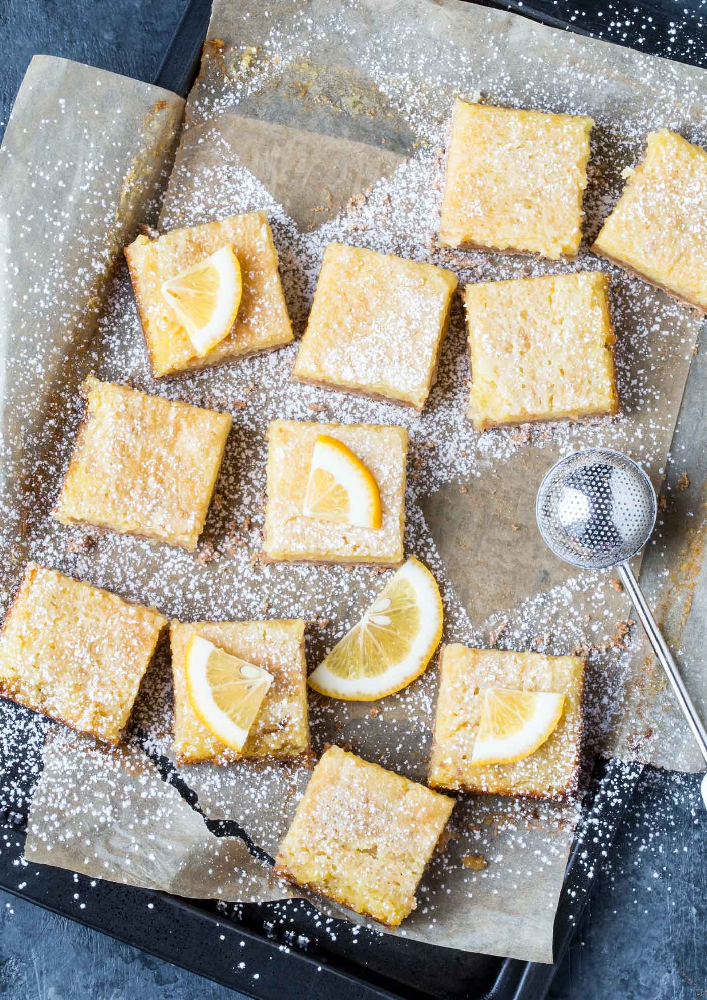 Top down shot of cut Coconut Lemon Bars on parchment paper. Dusted with powdered sugar and garnish with fresh lemon slices.