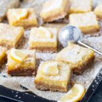 Sheet pan filled with cut squares of Coconut Lemon Bars dusted with powdered sugar and topped with fresh lemon slices.