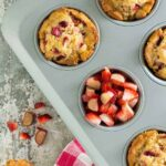 A muffin pan filled with muffins, with strawberry and rhubarb.