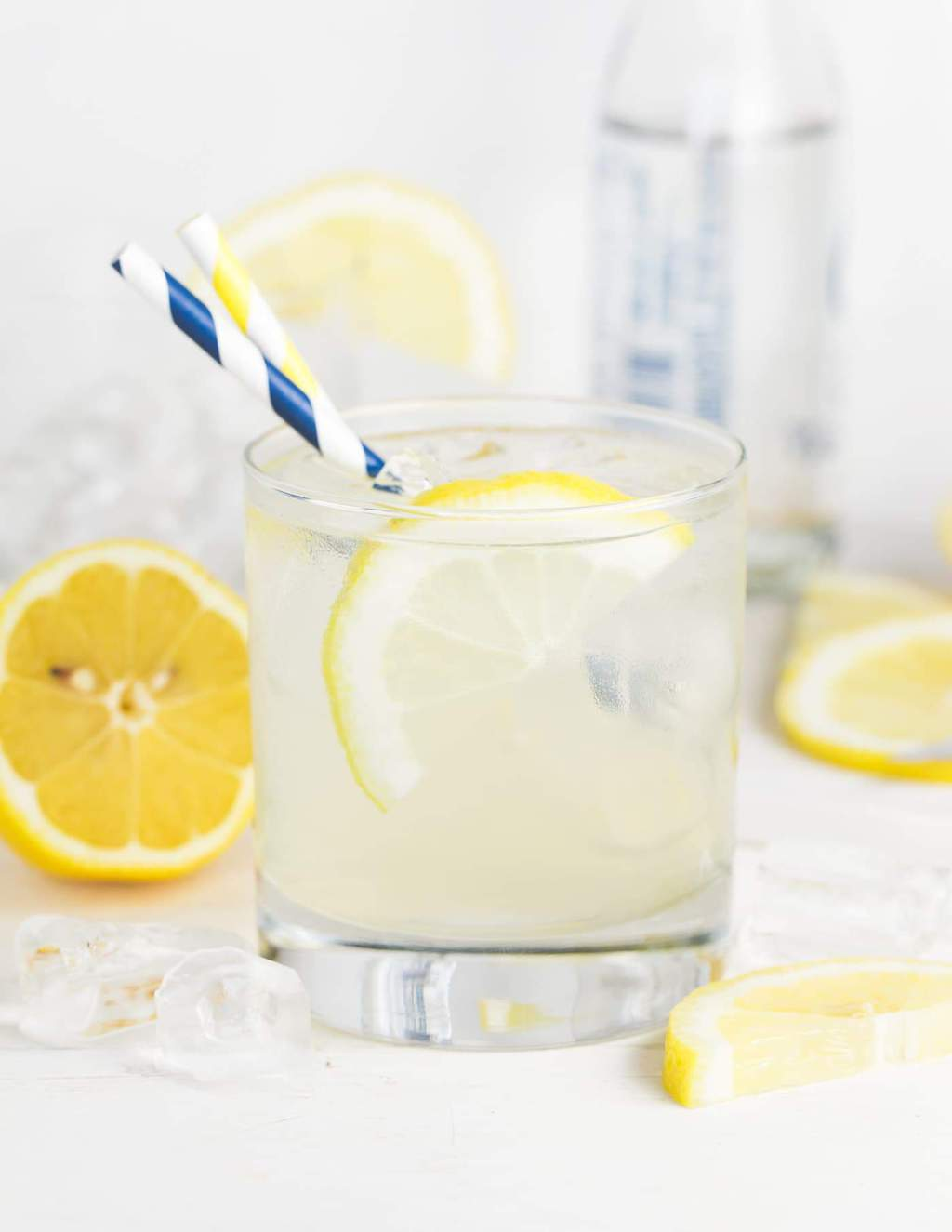 Lowball glass of vodka and elderflower lemonade. Garnished with lemon slices and blue and white striped straws.