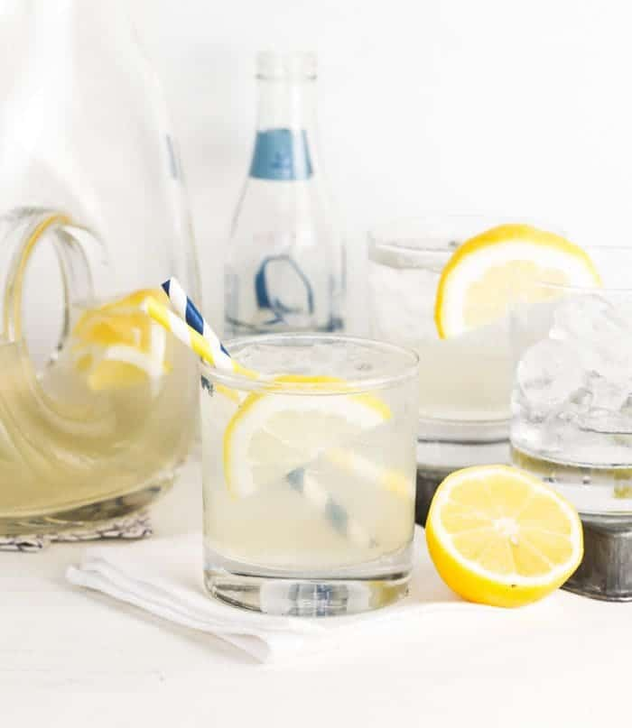 Pitcher of Vodka Elderflower Lemonade to serve a group. Low ball glasses filled with ice and garnished with lemon slices and striped straws.