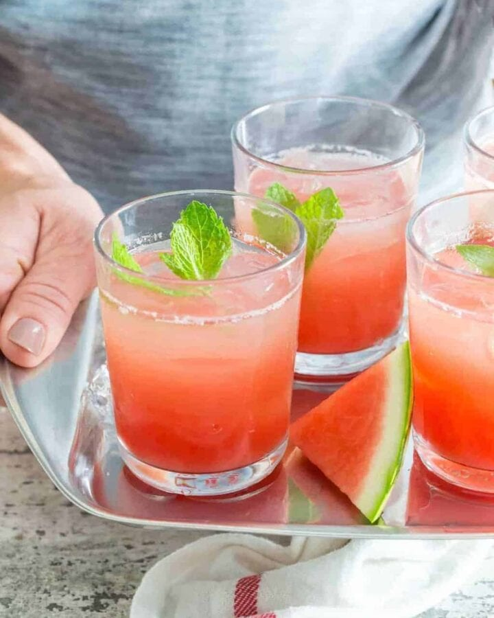 Person holding tray of watermelon gin punch in glasses.