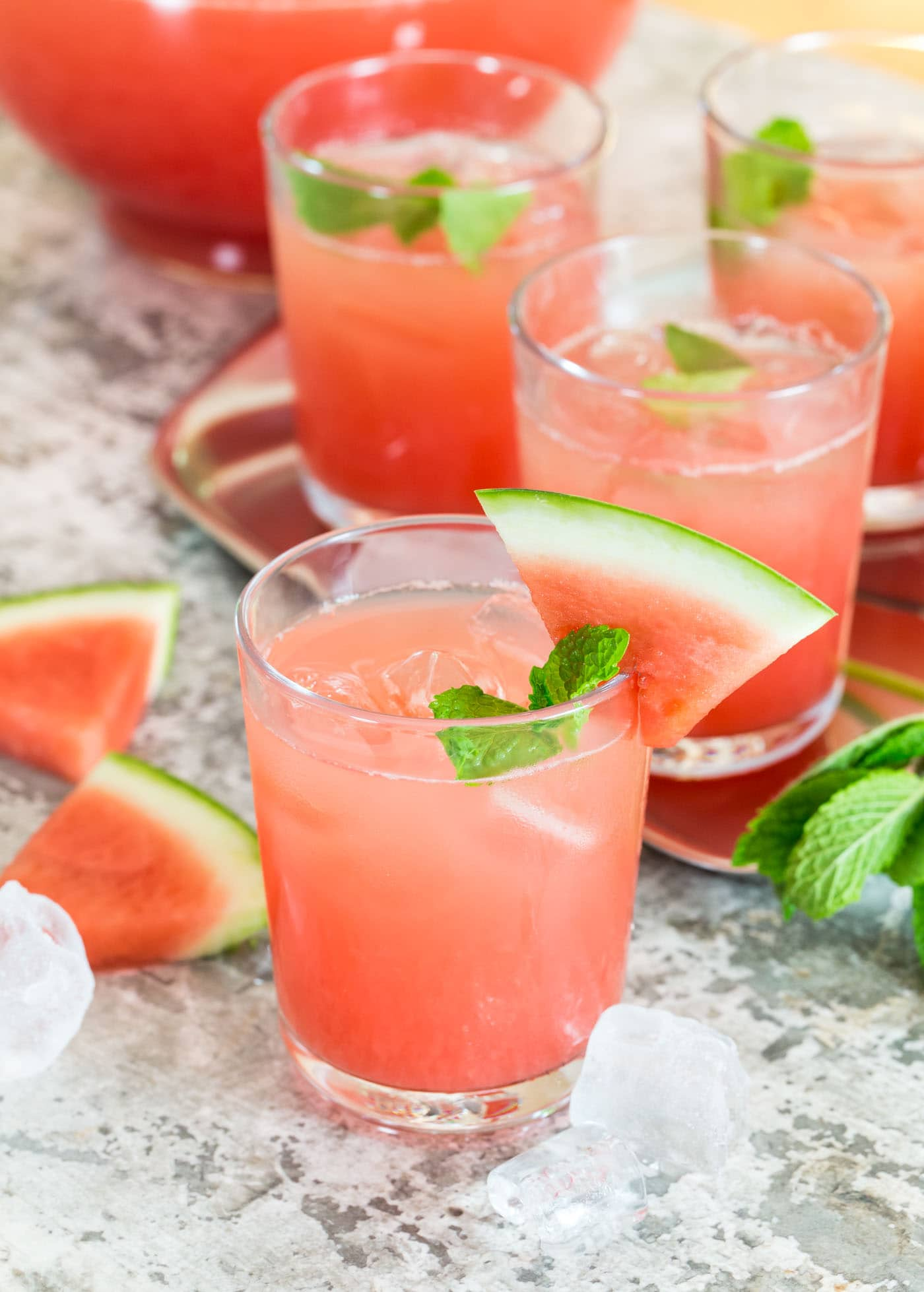 Cups of punch on tray with watermelon and mint.
