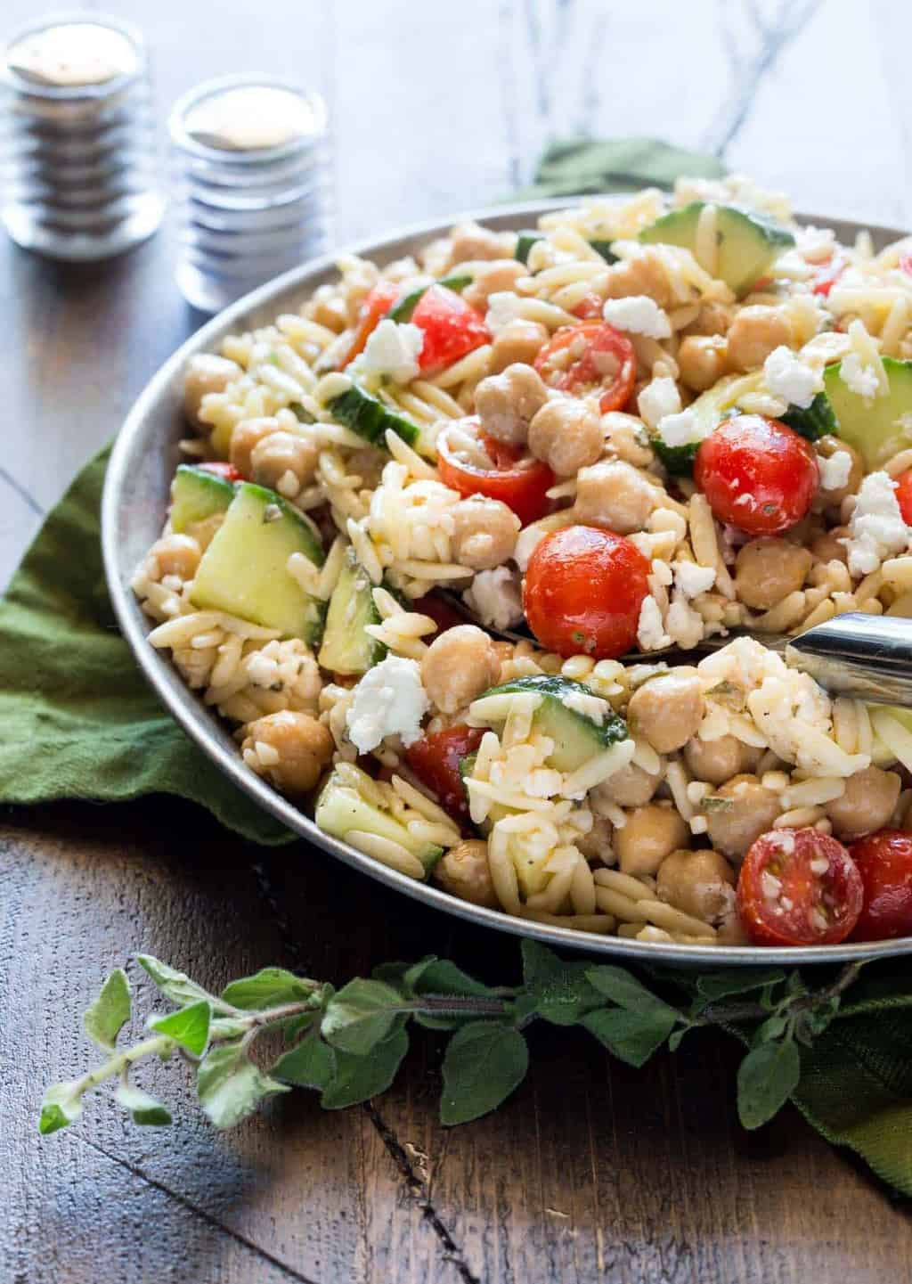Silver bowl filled with Orzo and Chickpea Salad, cucumbers, tomatoes, fresh oregano and goat cheese.