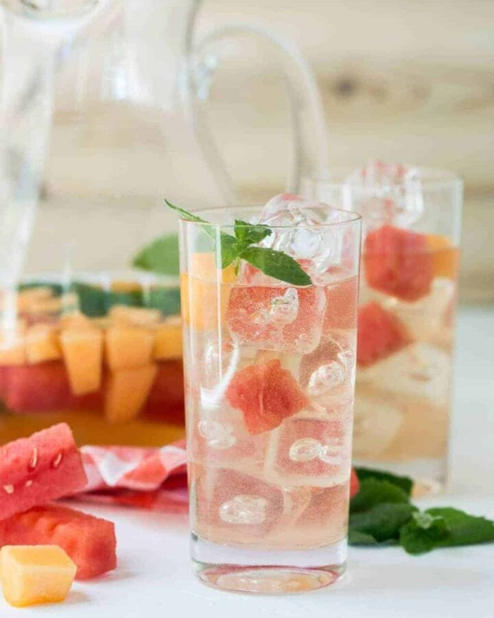 Elderflower Sangria in high ball glass with watermelon and cantaloupe cubes and mint leaves.
