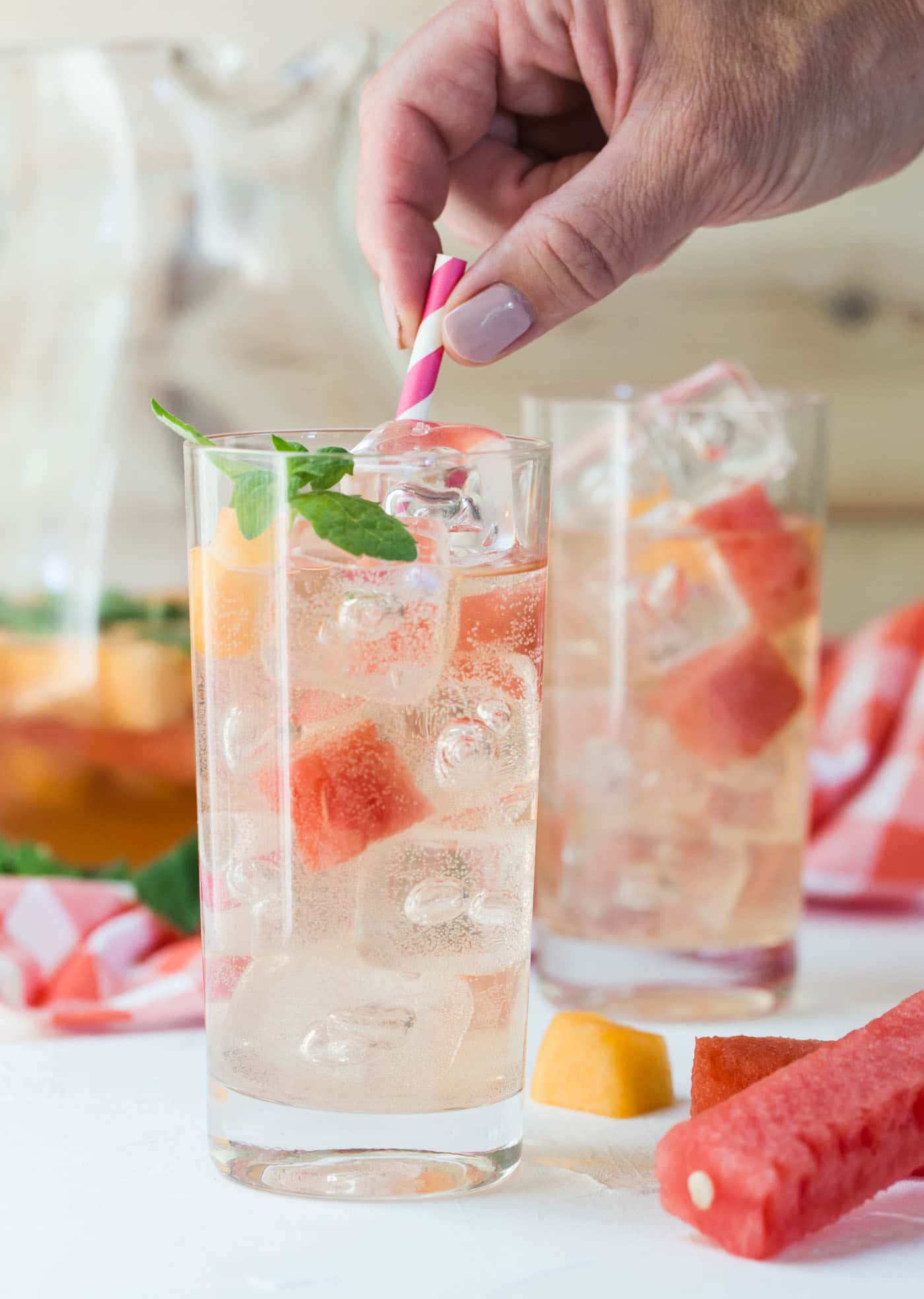 Rosé Elderflower Sangria over ice in a high ball glass served with melon balls and mint leaves! Perfect batch cocktail!