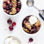 Ramekins of cherry crisp on a table, with ice cream.