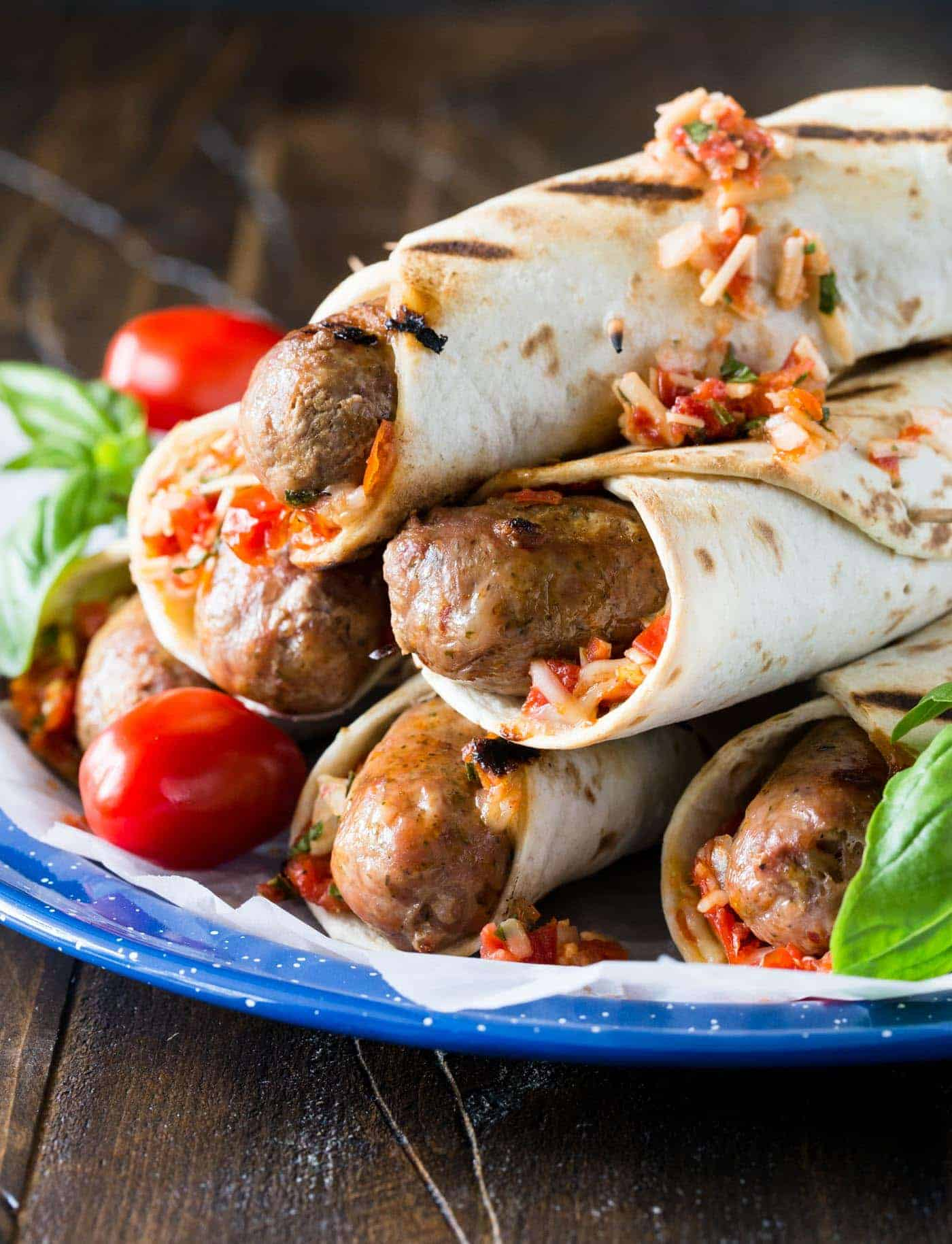 Picture of Grilled Italian Sausages on a blue plate. Sausages are wrapped in grilled flatbreads and garnished with a roasted tomato, asiago cheese and basil relish.