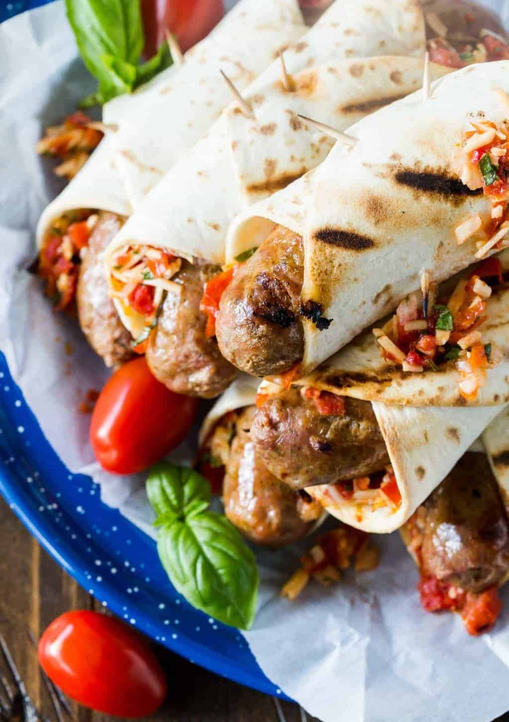 Picture of Grilled Italian Sausages piled high on a blue plate. Sausages are wrapped in grilled flatbreads and garnished with a roasted tomato, asiago cheese and basil relish.