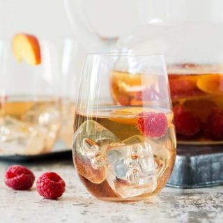 Glass of Peach Rosé Sangria with peach slices and raspberries floating in the glass. Pitcher of sangria in the background.